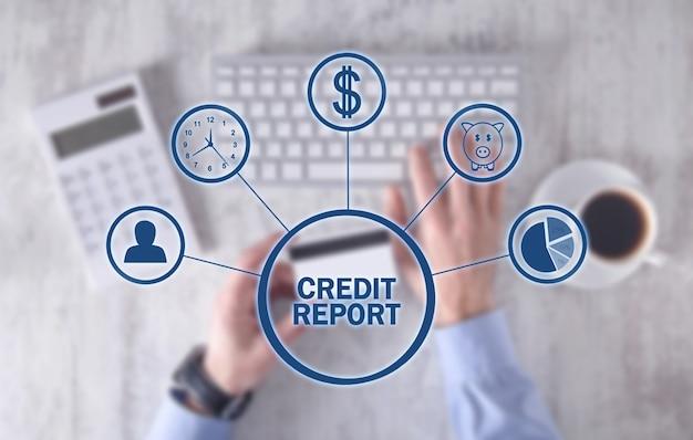 Mężczyzna trzyma kartę kredytową i za pomocą klawiatury. raport kredytowy