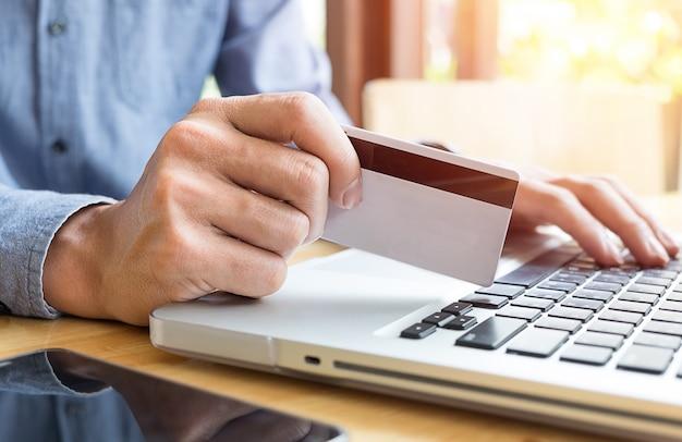 Mężczyzna trzyma kartę kredytową w ręku i wprowadzając kod zabezpieczający za pomocą klawiatury laptopa