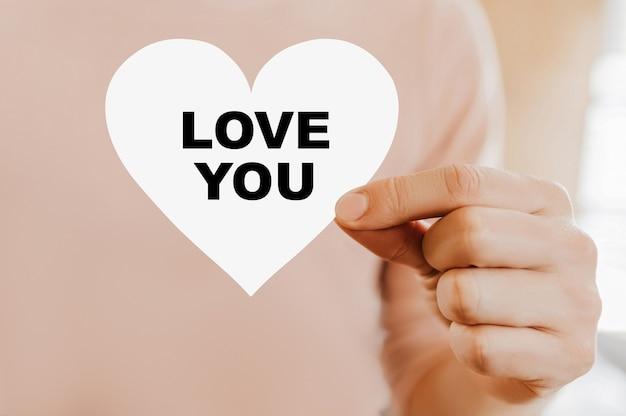 Mężczyzna trzyma kartę miłości w kształcie serca z miłością do ciebie
