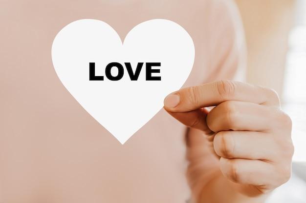 Mężczyzna trzyma kartę miłości w kształcie serca z miłością