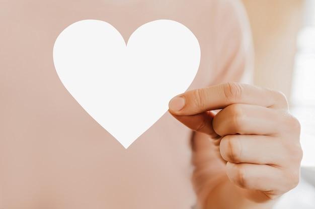 Mężczyzna trzyma kartę miłości w kształcie serca z pustym tłem