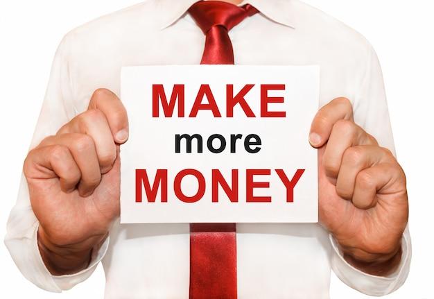 Mężczyzna trzyma kartę z tekstem zarabiaj więcej pieniędzy.