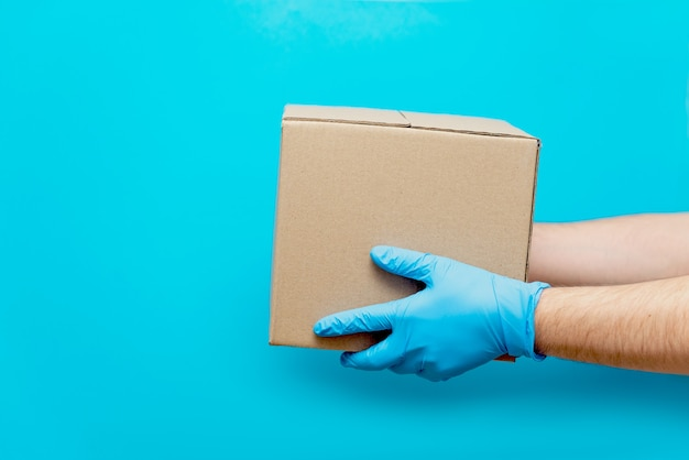Mężczyzna trzyma karton ręką w gumowej rękawiczce. ochrona przed covid-19. bezpieczna dostawa towarów podczas epidemii koronawirusa.