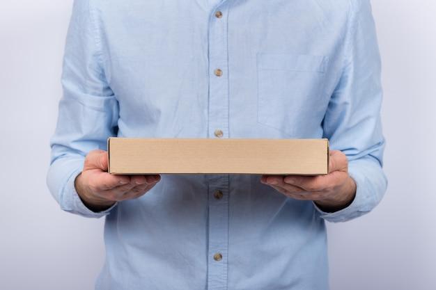 Mężczyzna trzyma kartonowe płaskie pudełko. dostawa pizzy. przesyłka kurierska do domu