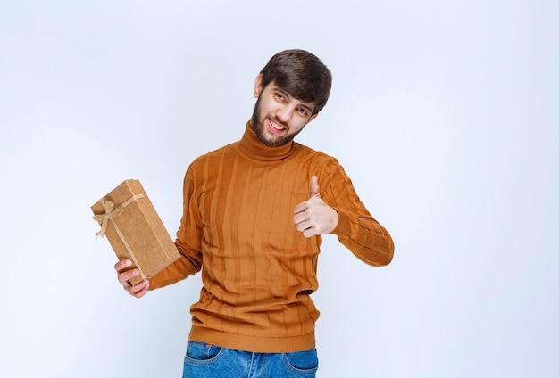Mężczyzna trzyma kartonowe pudełko i pokazuje znak przyjemności.