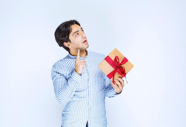 Mężczyzna trzyma kartonowe pudełko z czerwoną wstążką i myśli o podjęciu decyzji. zdjęcie wysokiej jakości