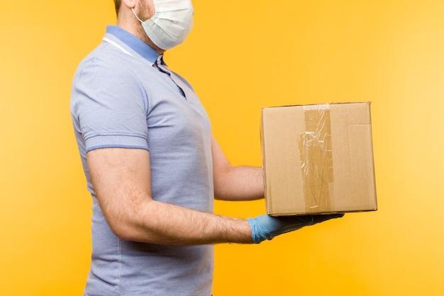 Mężczyzna trzyma kartony w gumowych rękawiczkach medycznych i masce. koncepcja dostarczania kwarantanny podczas pandemii koronawirusa