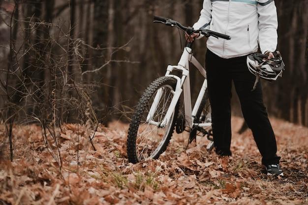 Mężczyzna trzyma kask do jazdy na rowerze z miejsca na kopię