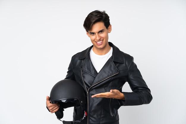 Mężczyzna trzyma kask motocyklowy wyciągając ręce z boku na zaproszenie