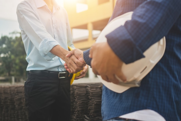 Mężczyzna trzyma kask są uścisnąć dłoń na koncepcji budowy witryny pracownik biznesowy pracy zespołowej