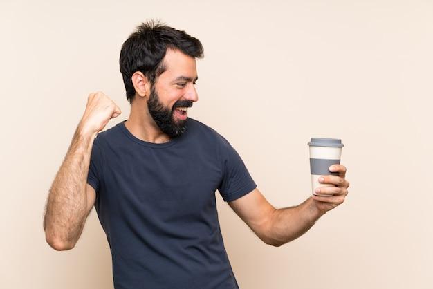 Mężczyzna trzyma kawę świętuje zwycięstwo z brodą
