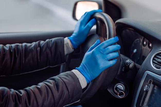 Mężczyzna trzyma kierownicę samochodu w ochronne rękawice medyczne. ręce z bliska. bezpieczna jazda taksówką podczas koronawirusa pandemicznego. chroń kierowcę i pasażerów przed bakteriami i wirusami.