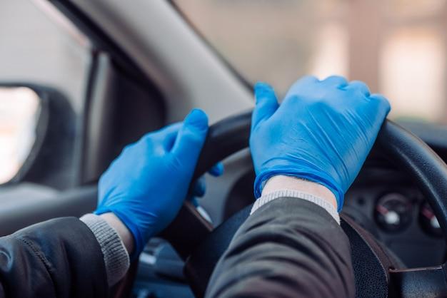 Mężczyzna trzyma kierownicę samochodu w ochronne rękawice medyczne. ręce z bliska. bezpieczna jazda taksówką podczas koronawirusa pandemicznego.