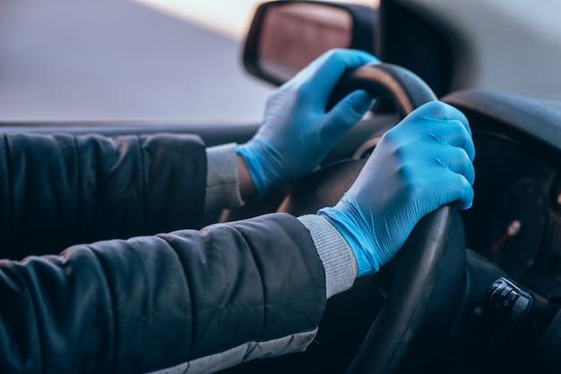 Mężczyzna trzyma kierownicę samochodu w ochronnych rękawiczkach medycznych. ręce z bliska. bezpieczna jazda taksówką podczas koronawirusa pandemicznego.