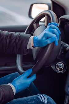 Mężczyzna trzyma kierownicę samochodu w ochronnych rękawiczkach medycznych. ręce z bliska