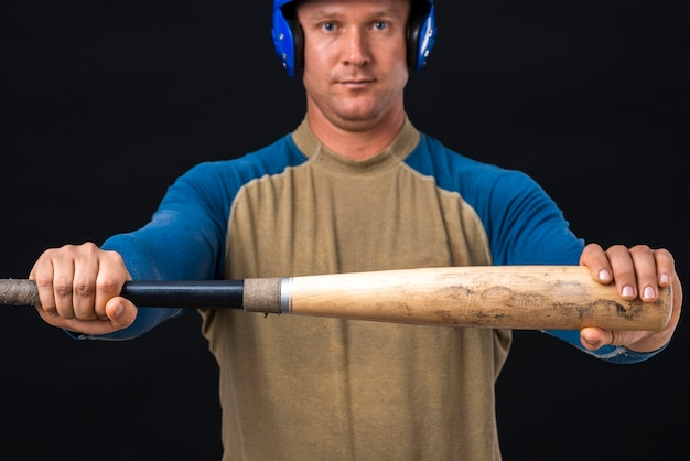 Mężczyzna trzyma kij bejsbolowy poziomo