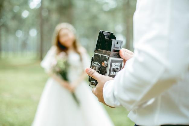 Mężczyzna trzyma klasyczną kamerę stoi obok swojej dziewczyny