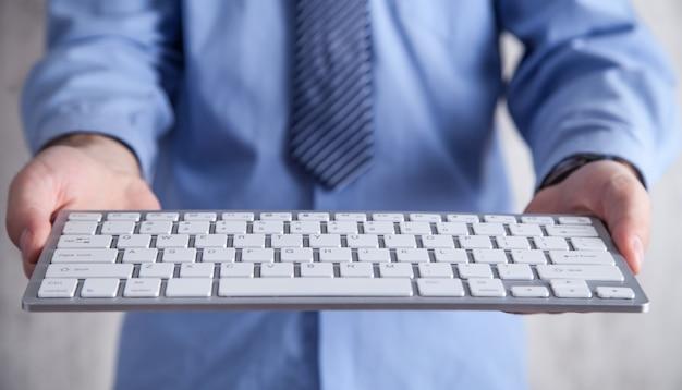 Mężczyzna trzyma klawiaturę komputera. technologia, biznes