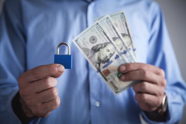Mężczyzna trzyma kłódkę z dolarów. zabezpieczenie finansowe