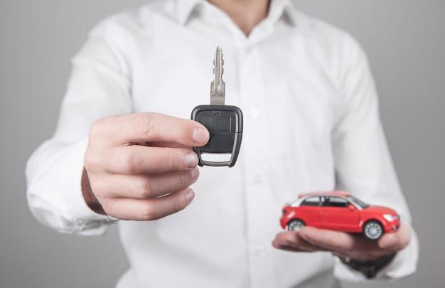 Mężczyzna trzyma kluczyk z samochodem w biurze.