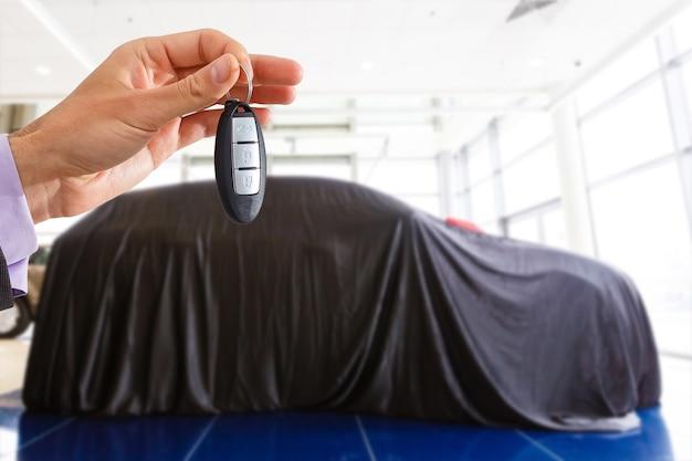 Mężczyzna trzyma kluczyki do samochodu z samochodem na tle