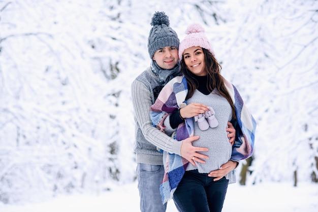 Mężczyzna trzyma kobiecy brzuch w ciąży i kobieta trzyma w ręku buty dziecięce, gdy stoją na śnieżnym zimowym parku