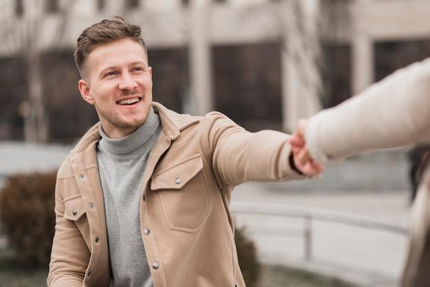 Mężczyzna trzyma kobiety rękę na zewnątrz