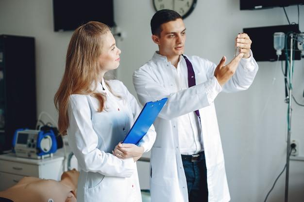 Mężczyzna trzyma kolbę do analizy pielęgniarka z teczką w ręku słucha lekarza studenci w szpitalnych fartuchach