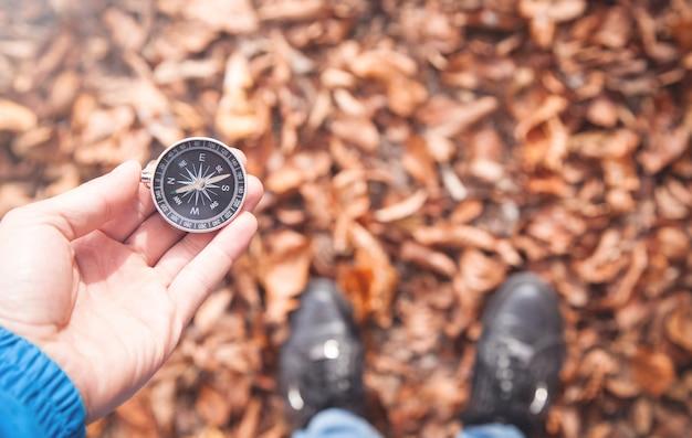 Mężczyzna trzyma kompas w lesie jesienią.
