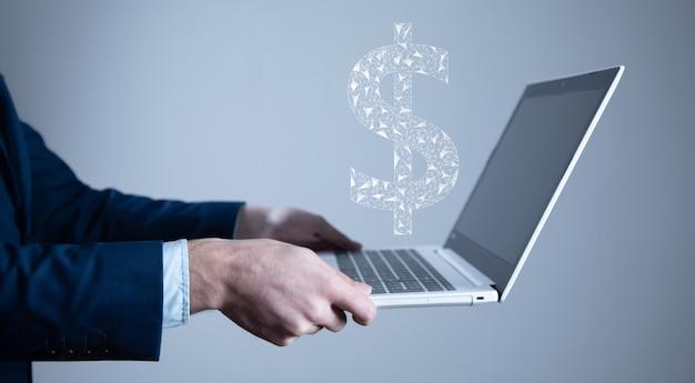 Mężczyzna trzyma komputer z cyfrowymi znakami dolara