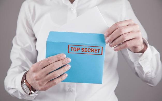 Mężczyzna trzyma kopertę z pieczęcią ściśle tajne.