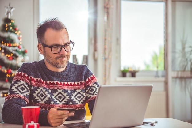 Mężczyzna trzyma kredytową kartę i używa laptopu domowego biuro