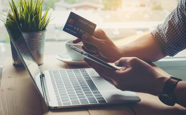 Mężczyzna trzyma kredytowej karty zapłatę robi zakupy online na mądrze telefonie
