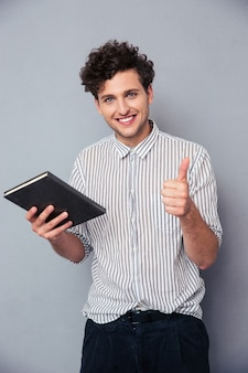 Mężczyzna trzyma książkę i pokazuje kciuk w górę