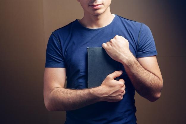 Mężczyzna trzyma książkę na brązowym tle
