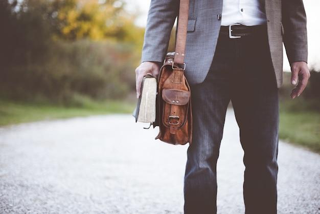 Mężczyzna trzyma książkę na drodze w ciągu dnia
