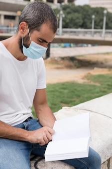 Mężczyzna trzyma książkę na zewnątrz podczas noszenia maski medycznej