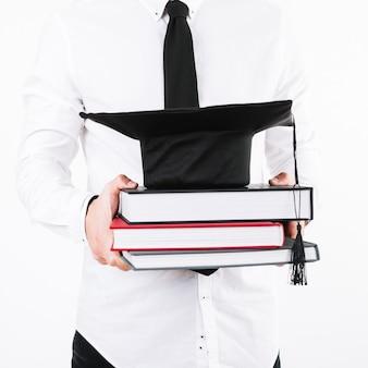 Mężczyzna trzyma książki i biret