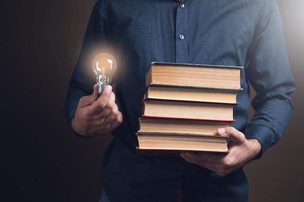 Mężczyzna trzyma książki i żarówkę. pomysły koncepcyjne z książek