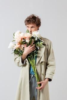 Mężczyzna trzyma kwiaty w płaszczu