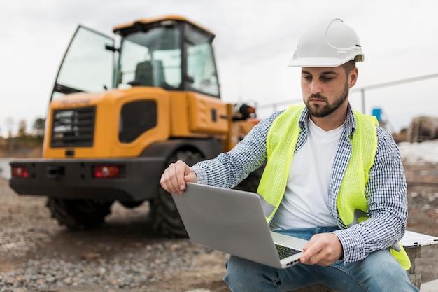 Mężczyzna trzyma laptopa na budowie