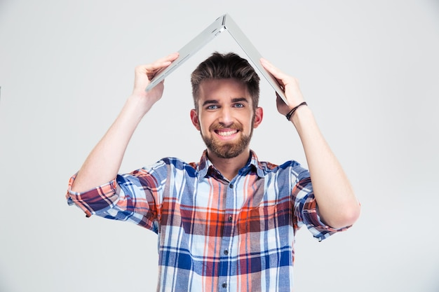 Mężczyzna trzyma laptopa na głowie jak dach domu
