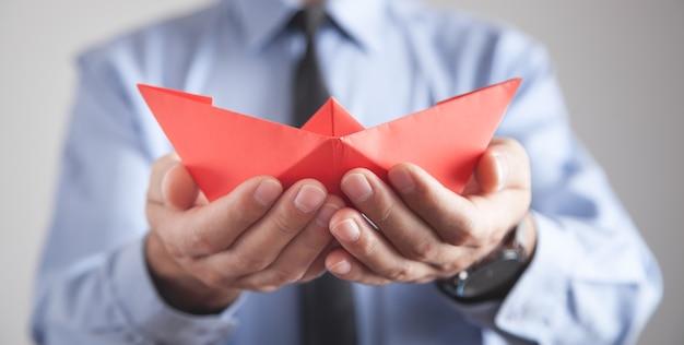 Mężczyzna trzyma łódź papieru czerwony origami