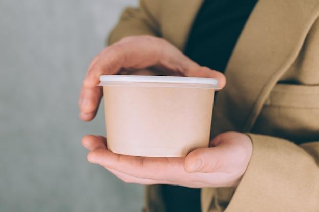 Mężczyzna trzyma makietę papierowego kubka na zupę, kawę i herbatę na lampce.