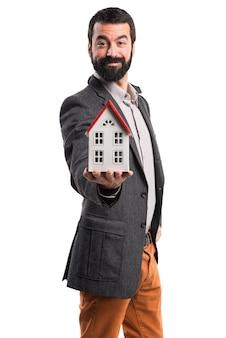 Mężczyzna trzyma mały dom
