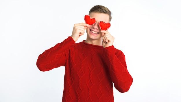 Mężczyzna trzyma małych serca przy oczami