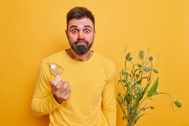 Mężczyzna trzyma maskę tlenową ma reakcję alergiczną na dziki kwiat wygląda z szokiem na twarzy cierpi na objawy alergii nosi swobodny sweter na żółtym tle
