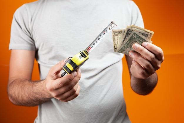 Mężczyzna trzyma miarkę i pieniądze na pomarańczowym tle