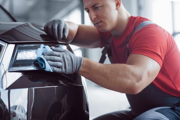 Mężczyzna trzyma mikrofibrę w dłoni i wygładza samochód. nowa maszyna jest przygotowywana do sprzedaży