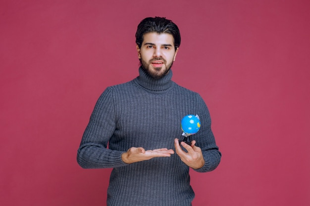 Mężczyzna trzyma mini kulę ziemską i robi prezentację na ten temat.